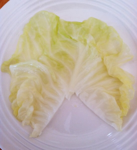 Cut the roughest part of stem out of the cabbage leaf about 2 inches from the bottom. This is what it should look like. Put your filling at the top. Roll once. Fold in both outer edges and then continue to roll up until they are in a nice, neat roll.